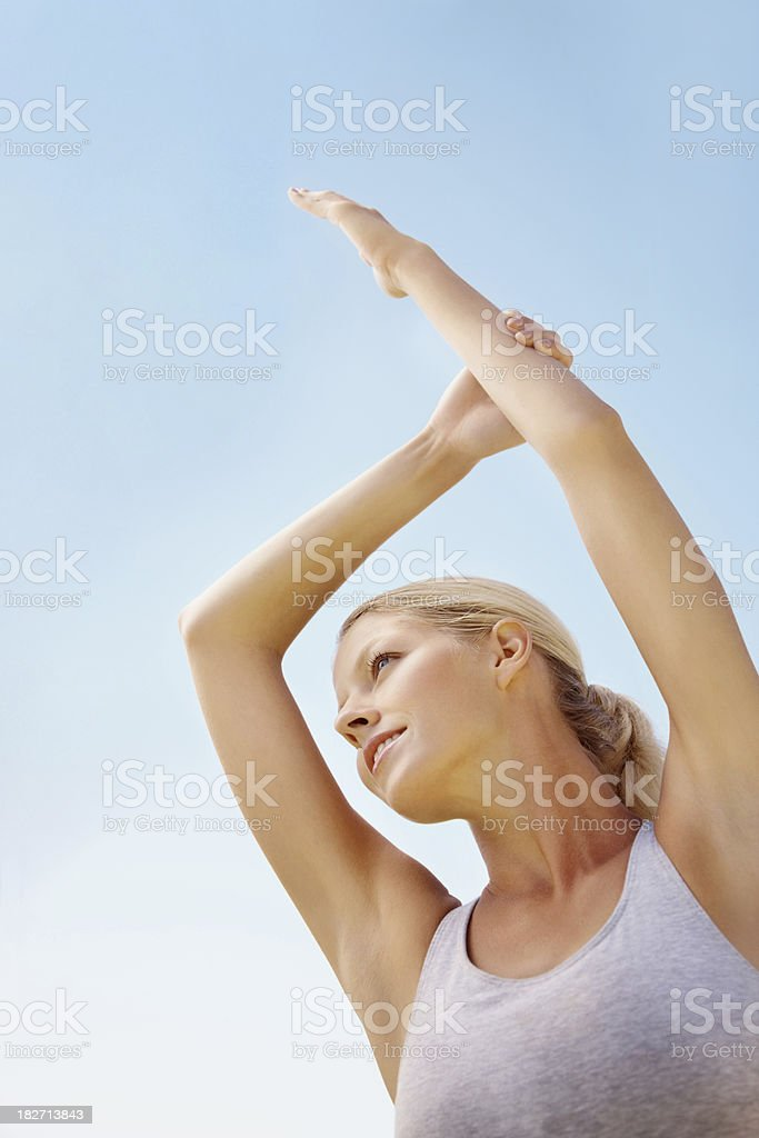 Woman doing stretching exercise against the blue sky royalty-free stock photo