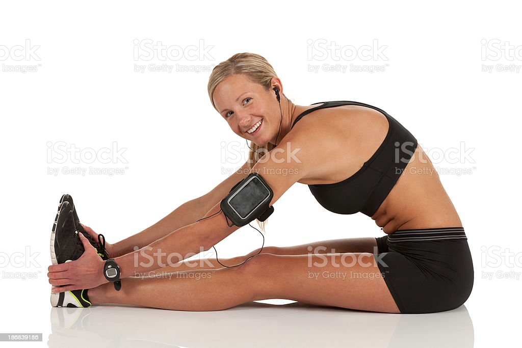 Woman doing stretching exercise with an mp3 player stock photo