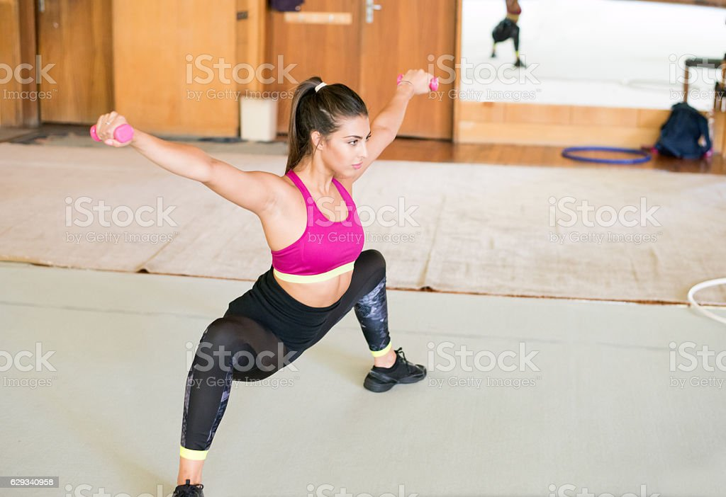 Woman doing suats in a fitness center stock photo