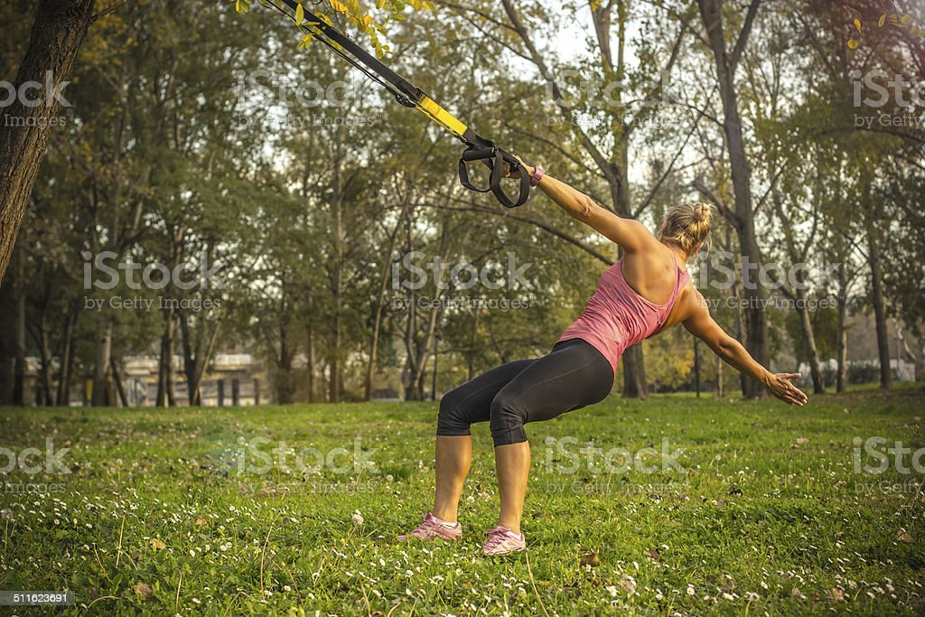 Woman doing suspension training in the park stock photo