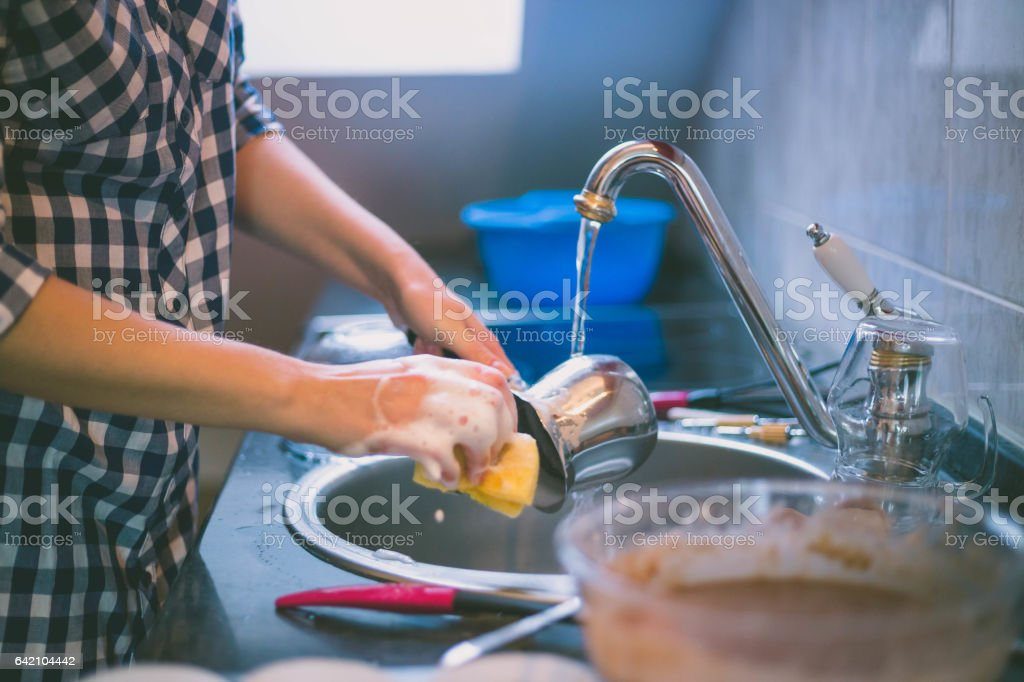 woman doing the washing up in modern kitchen stock photo