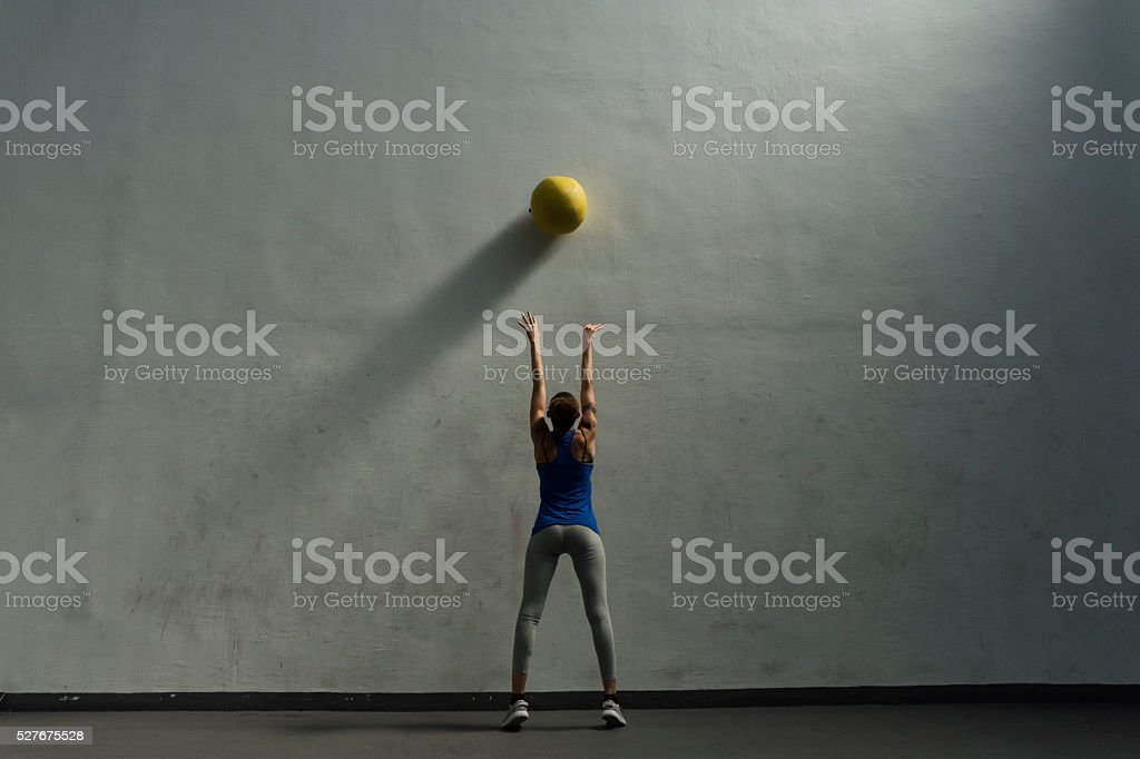 Woman doing wall ball exercise stock photo