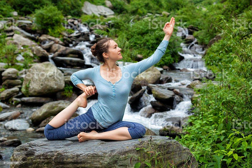 Woman doing yoga asana at tropical waterfall stock photo