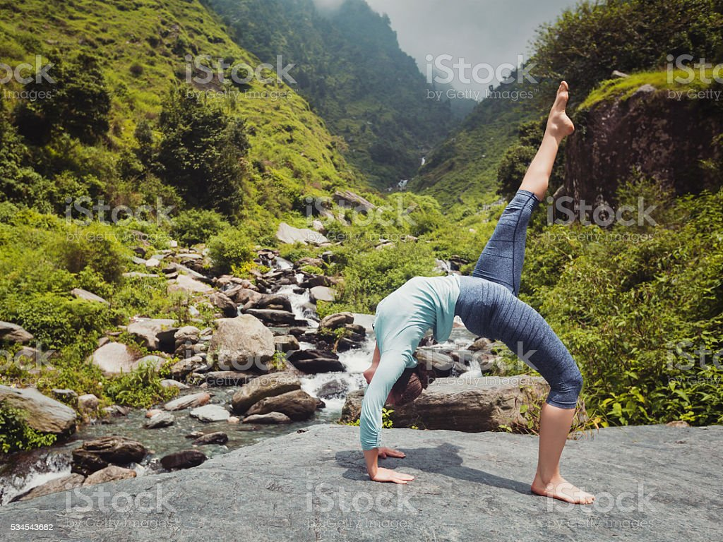 Woman doing yoga asana at waterfall stock photo