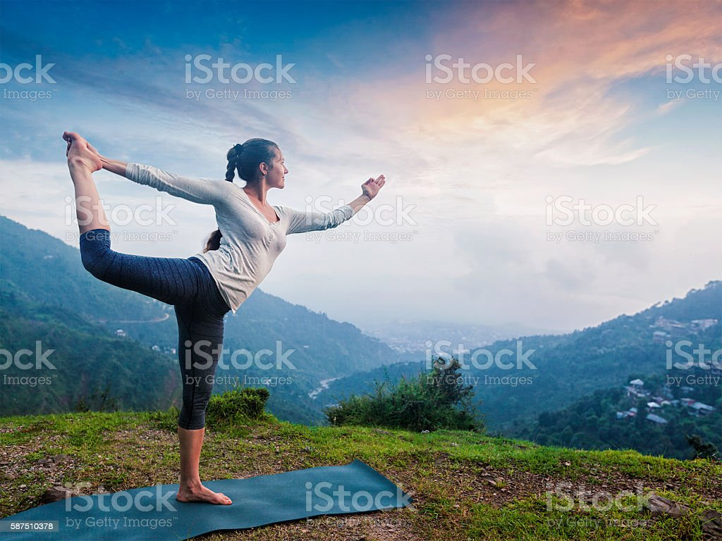 Woman doing yoga asana Natarajasana outdoors at waterfall stock photo