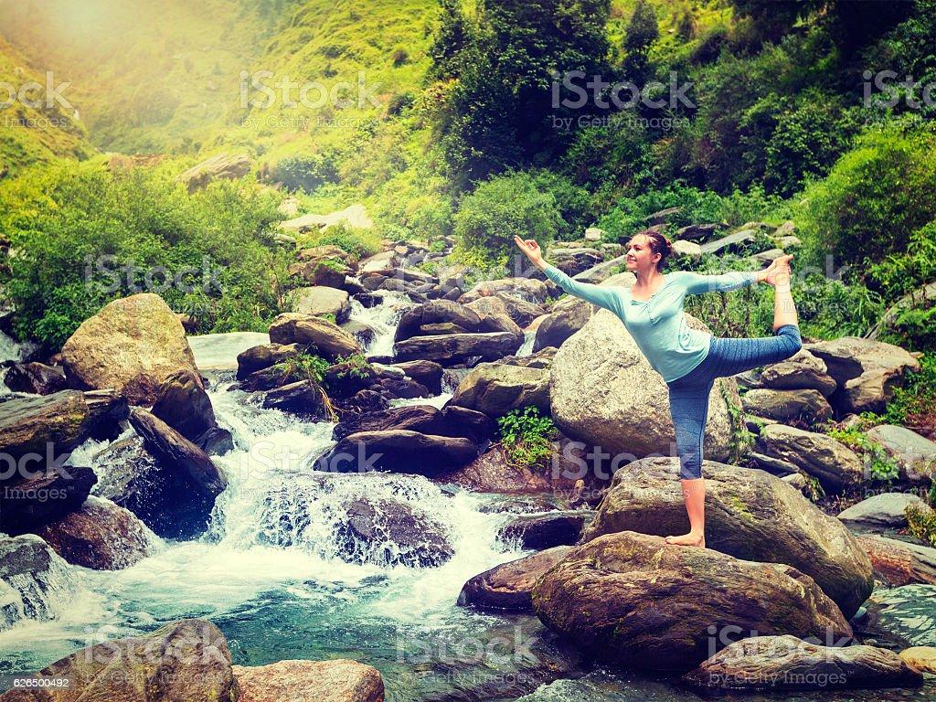Woman doing yoga asana Natarajasana outdoors at waterfall stock photo