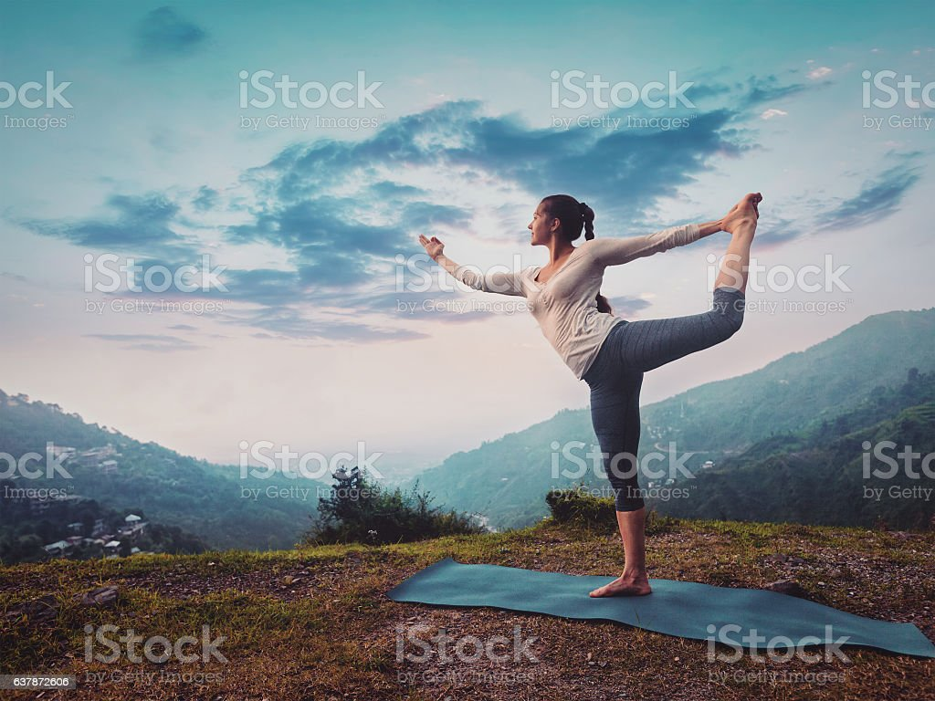 Woman doing yoga asana Natarajasana outdoors on sunset stock photo