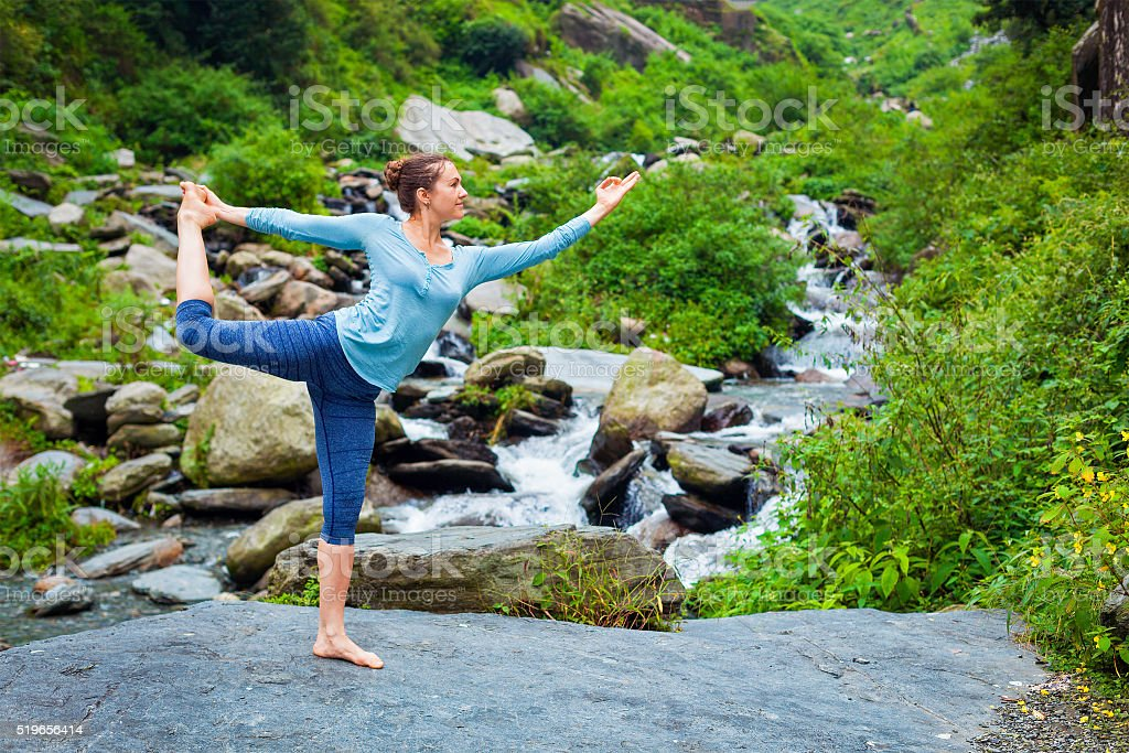 Woman doing yoga asana outdoors at waterfall stock photo