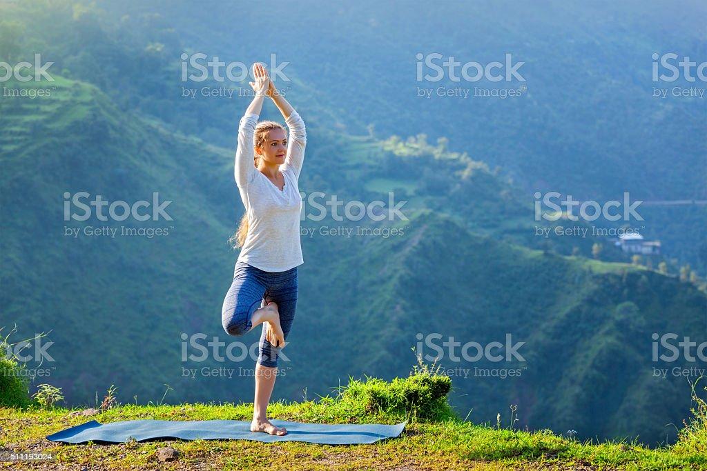 Woman doing yoga asana tree pose outdoors stock photo