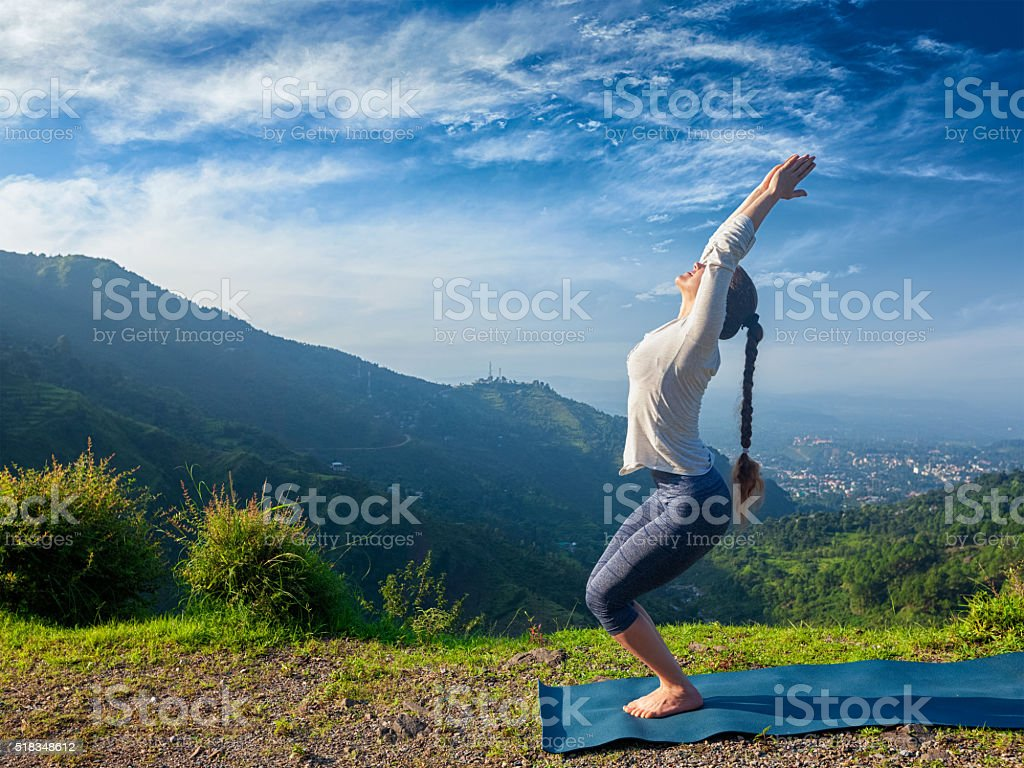 Woman doing yoga asana Utkatasana outdoors stock photo