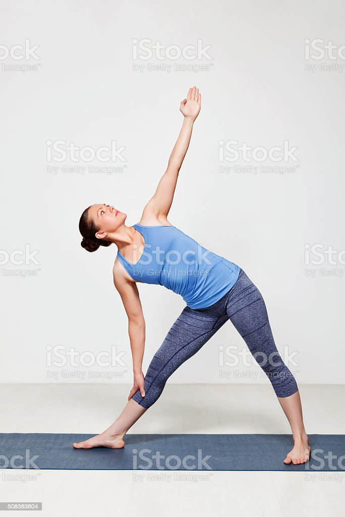 Woman doing yoga asana utthita trikonasana stock photo