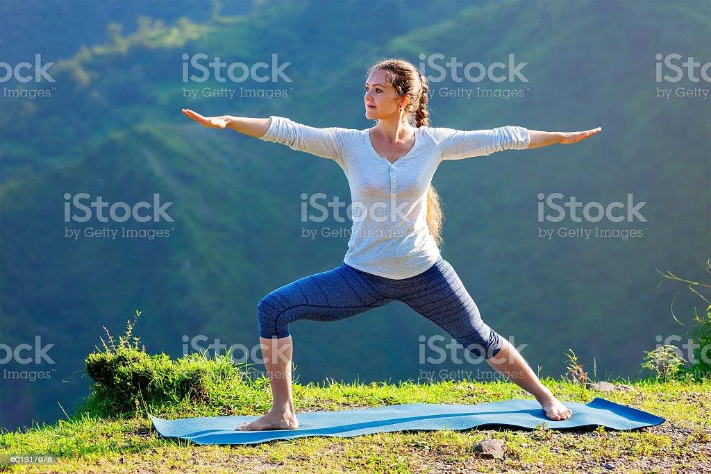Woman doing yoga asana Virabhadrasana 2 - Warrior pose outdoors stock photo