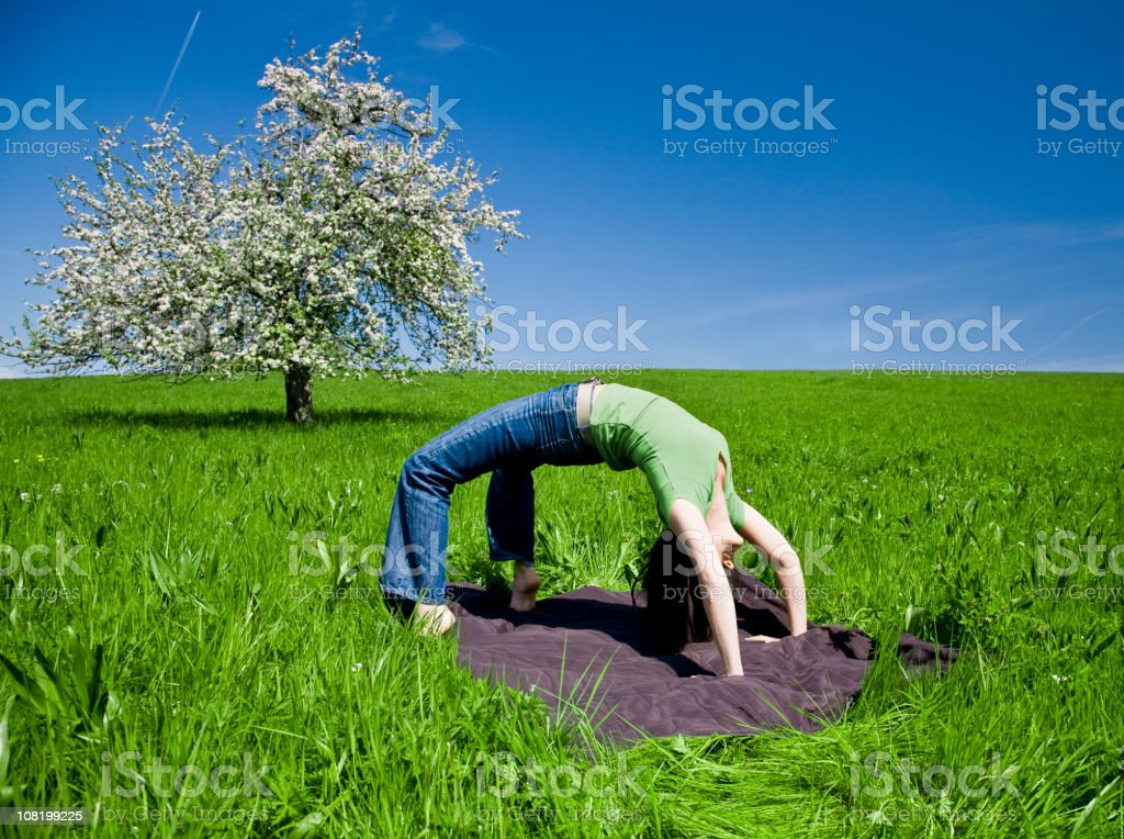 Woman Doing Yoga Bridge Pose in Green Blooming Meadow stock photo