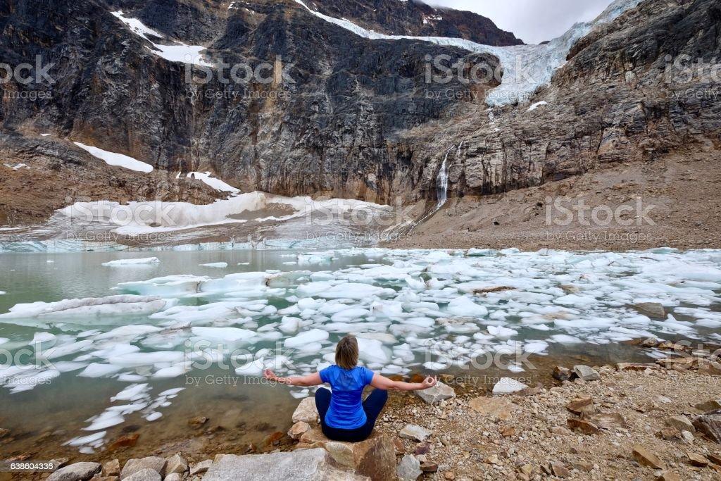 Woman doing yoga by lake. stock photo