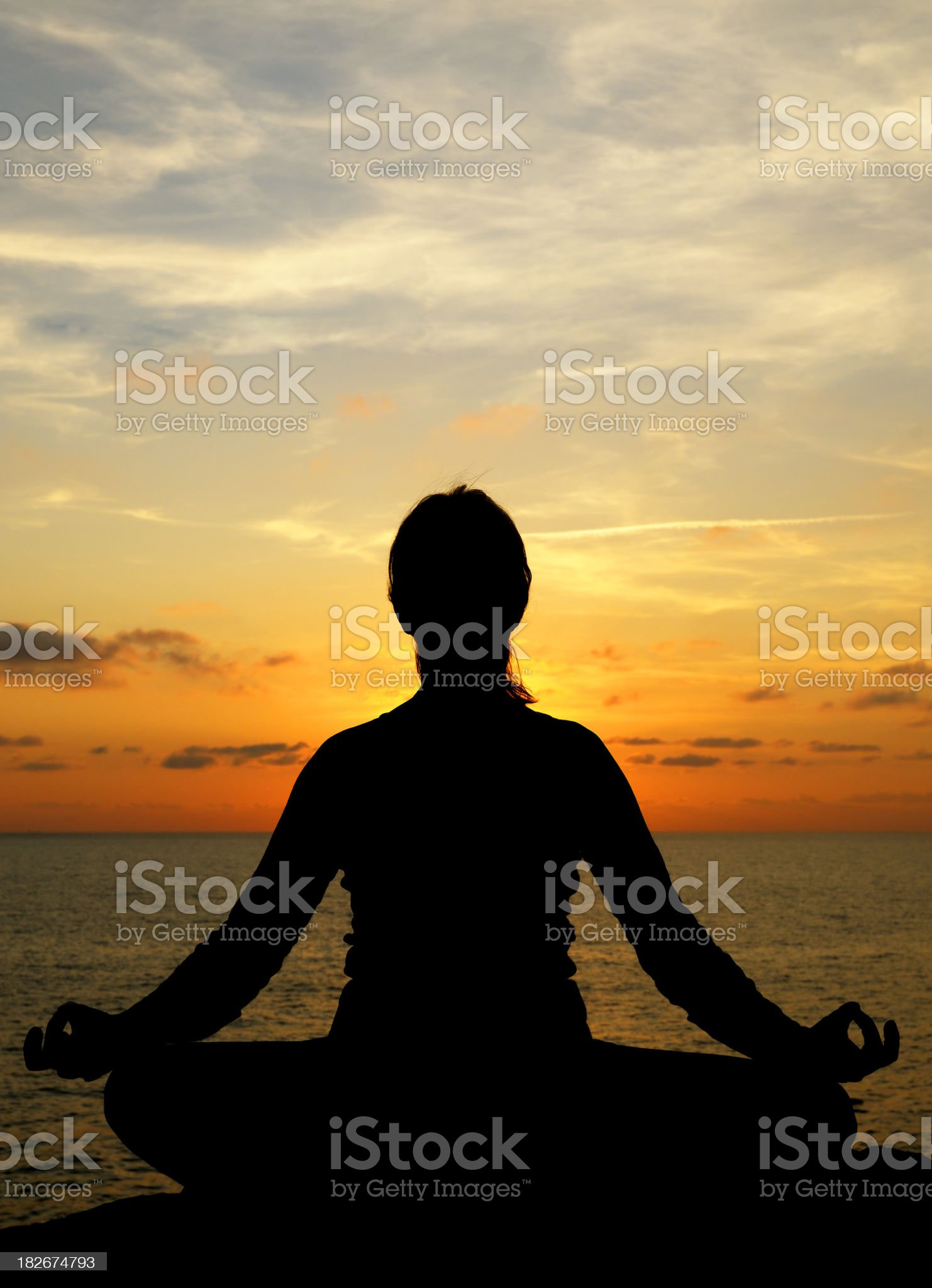 Woman Doing Yoga by the Sea at Sunset royalty-free stock photo