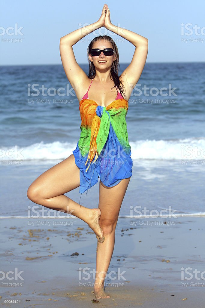 Woman doing yoga exercise on the beach royalty-free stock photo