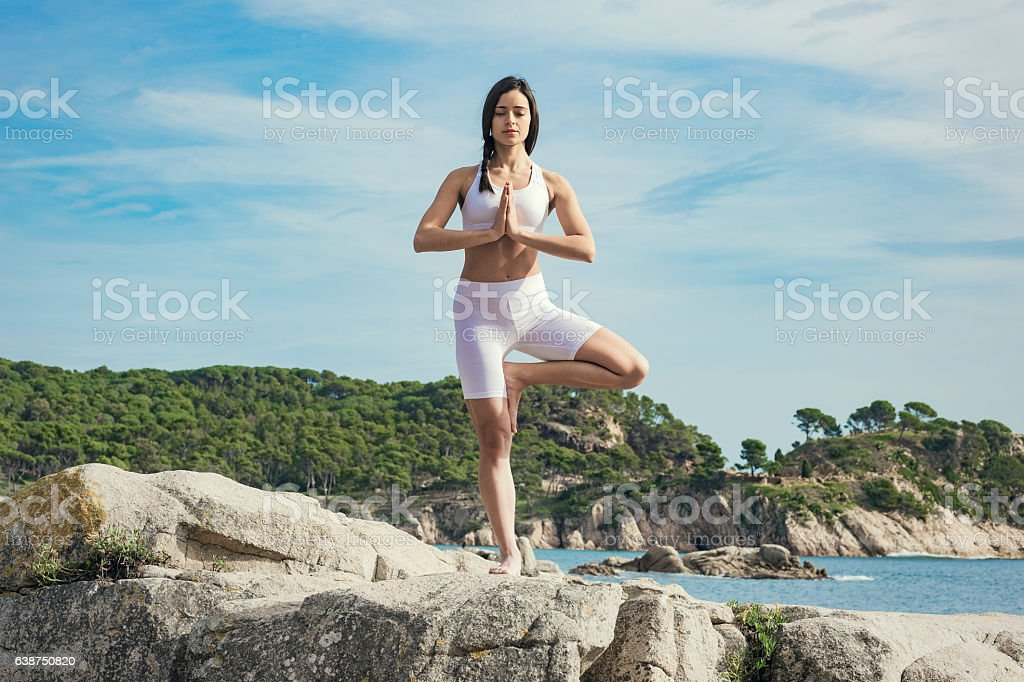 Woman doing yoga exercises at the sea stock photo