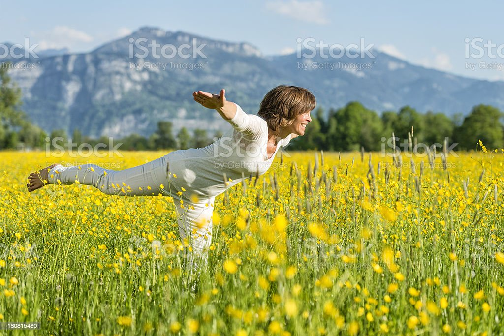 woman doing yoga exercises in flower meadow royalty-free stock photo