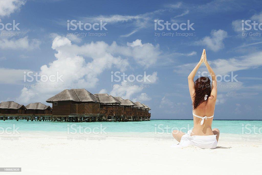 woman doing yoga exercises on the beach royalty-free stock photo