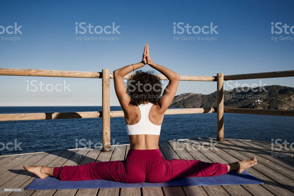 Woman doing yoga exercises outdoors stock photo