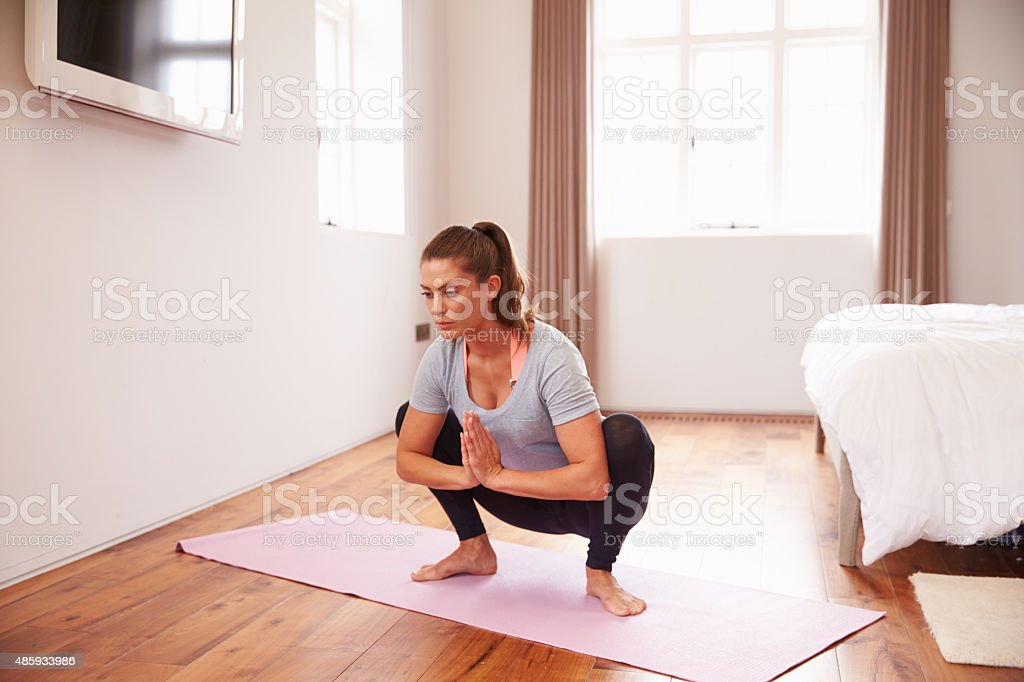 Woman Doing Yoga Fitness Exercises On Mat In Bedroom stock photo