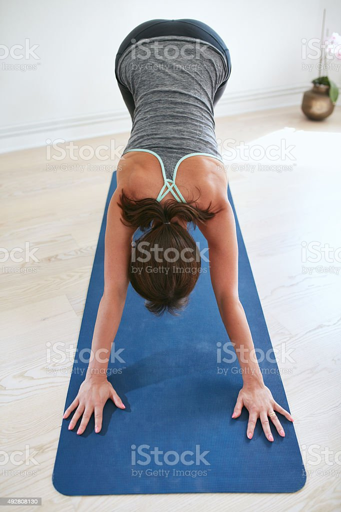 Woman doing yoga forward bend pose at gym. stock photo