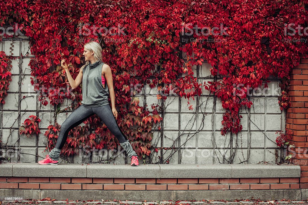 Woman doing yoga in city nature stock photo