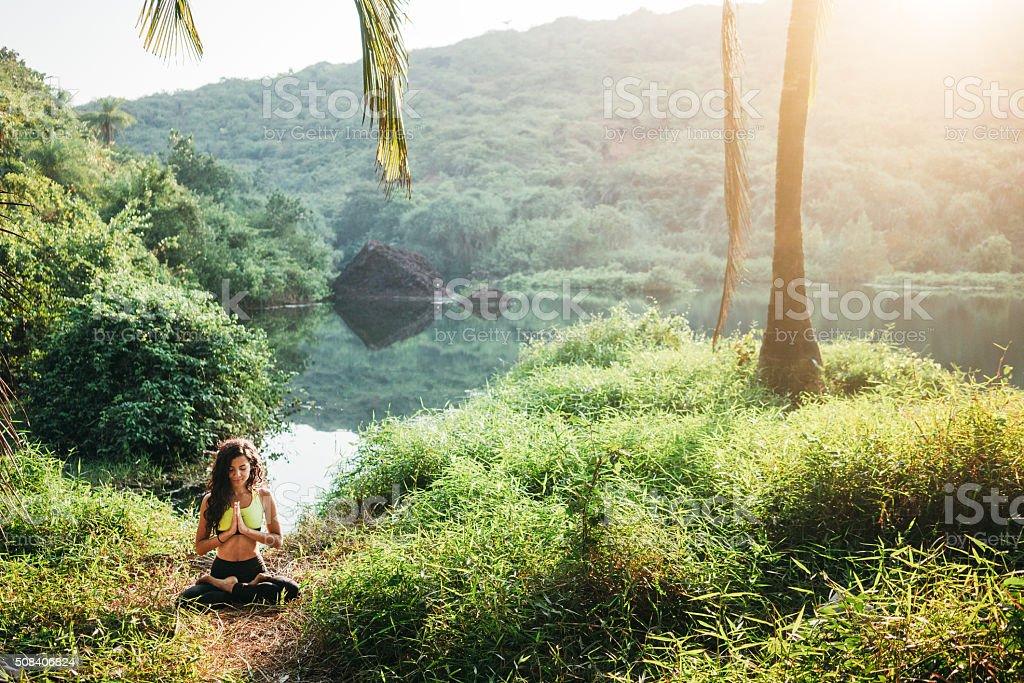 Woman doing yoga in jungles stock photo