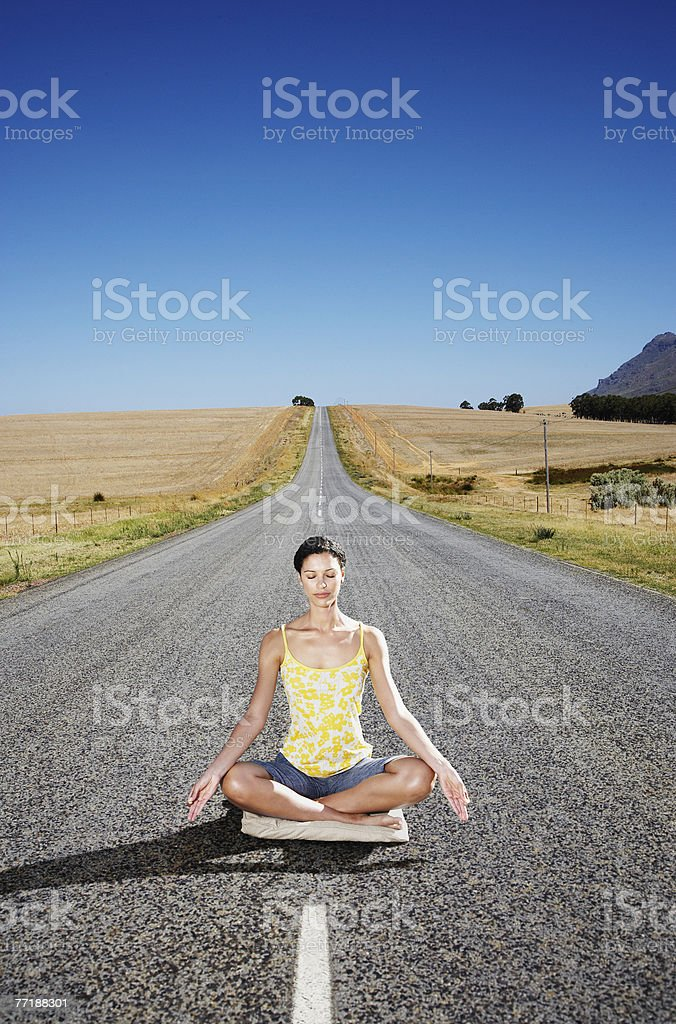 A woman doing yoga in the middle of the road royalty-free stock photo