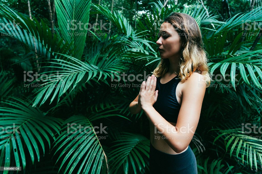 Woman doing yoga in tropical forest stock photo