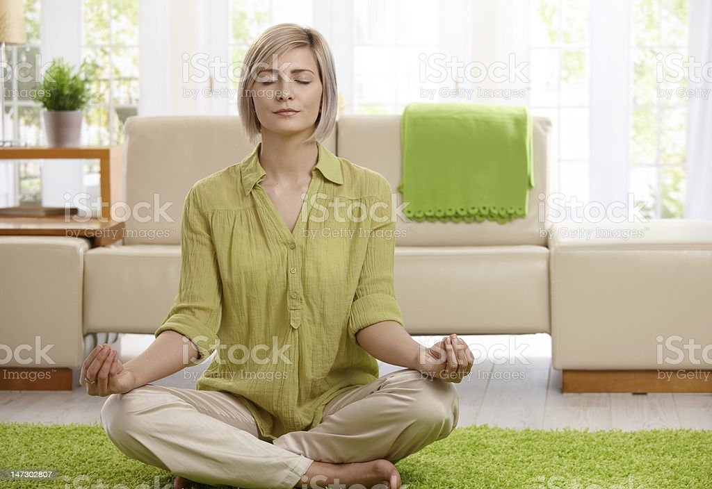 Woman doing yoga meditation at home royalty-free stock photo