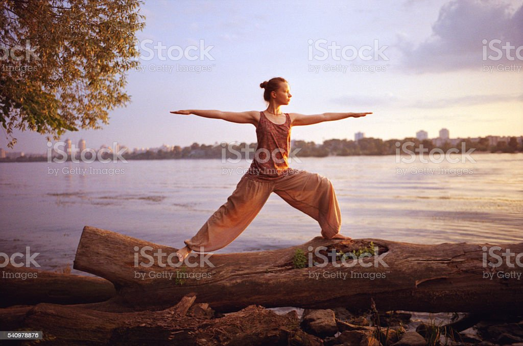 Woman doing yoga near the river stock photo