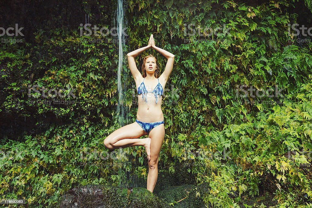 Woman Doing Yoga near Tropical Waterfall royalty-free stock photo