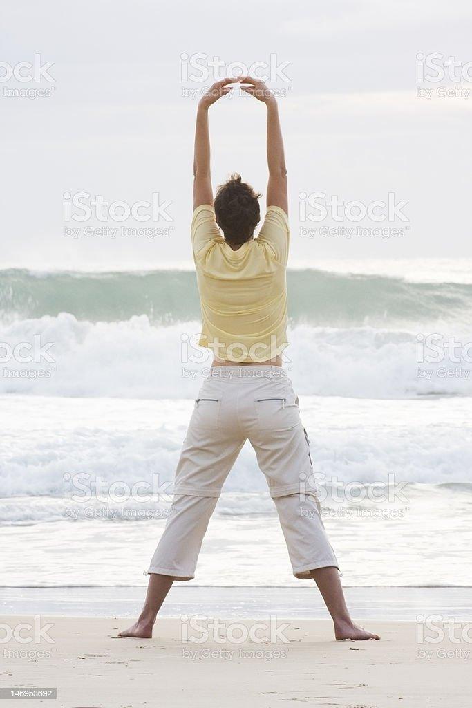 Woman doing yoga on a beach stock photo