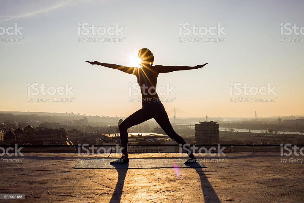 woman doing yoga on a rooftop stock photo