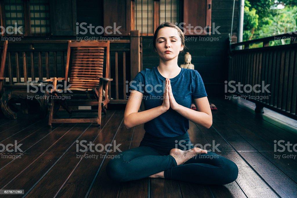Woman doing yoga on balcony stock photo