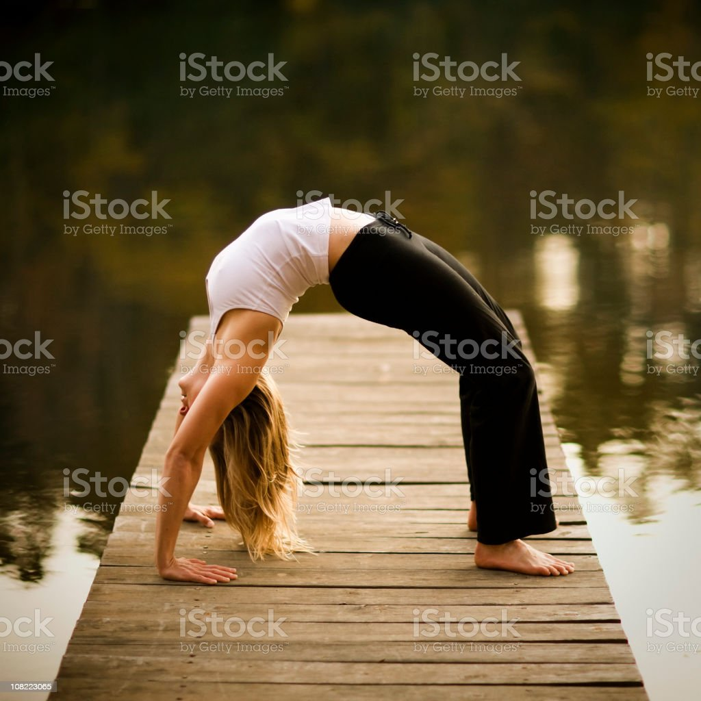 Woman Doing Yoga on Dock by Lake royalty-free stock photo