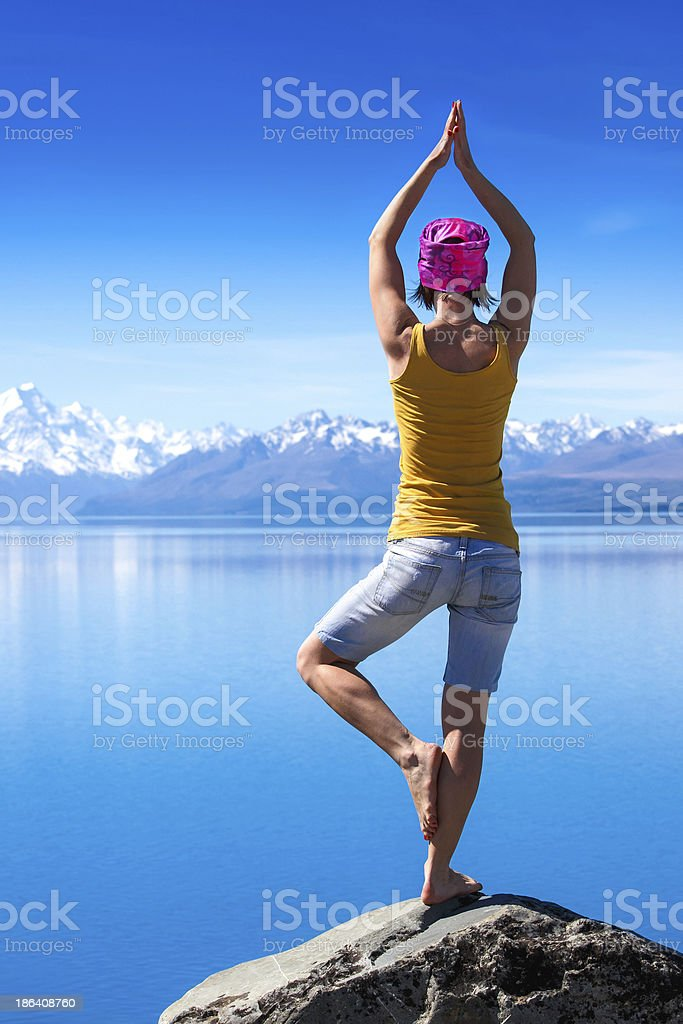 Woman doing yoga on rock royalty-free stock photo