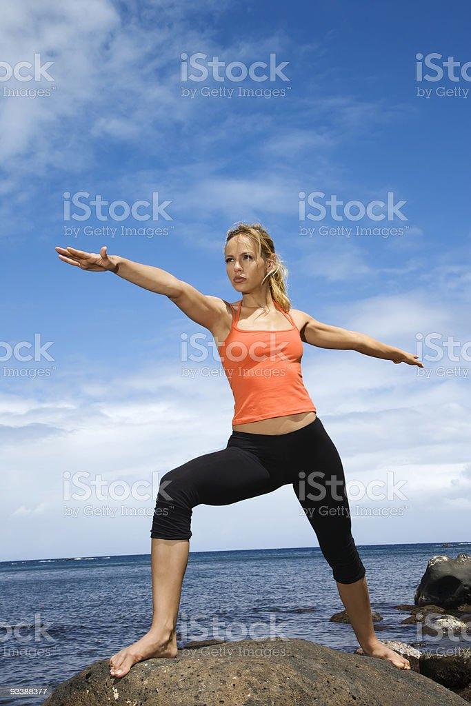 Woman doing yoga on rocky shore. royalty-free stock photo