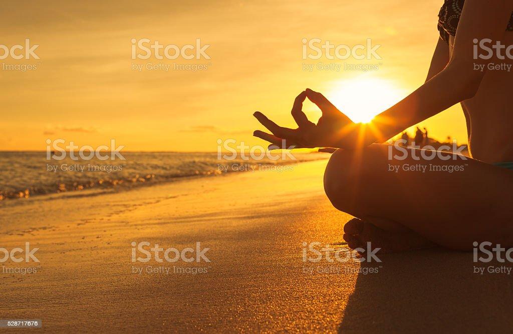 Woman doing yoga on the beach stock photo