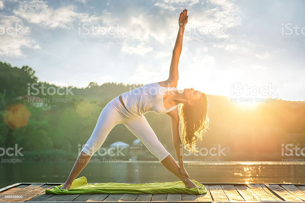 Woman doing yoga on the lake - beautiful lights stock photo