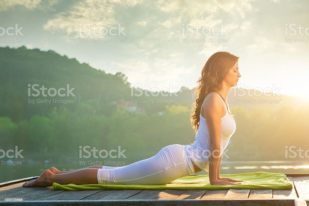 Woman doing yoga on the lake - relaxing in nature stock photo