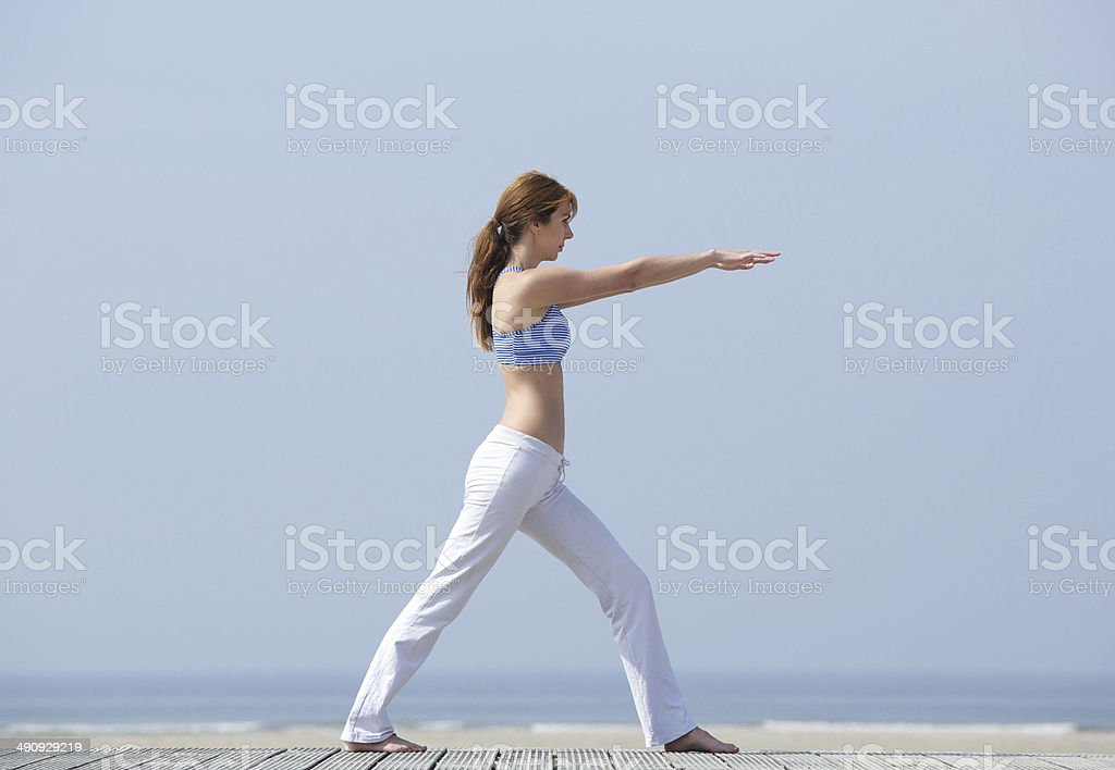 Woman doing yoga stretch at the beach royalty-free stock photo