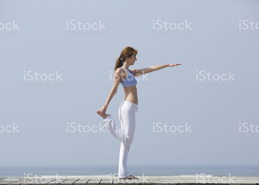 Woman doing yoga stretches at the beach royalty-free stock photo