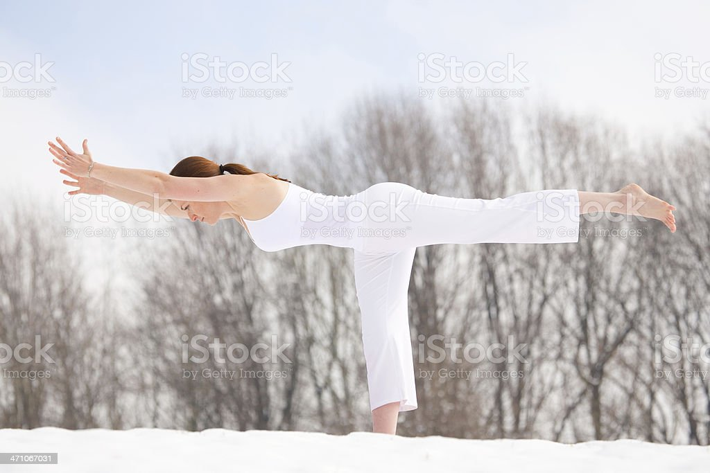 Woman doing Yogic 'Warrior 3' Pose in the snow royalty-free stock photo