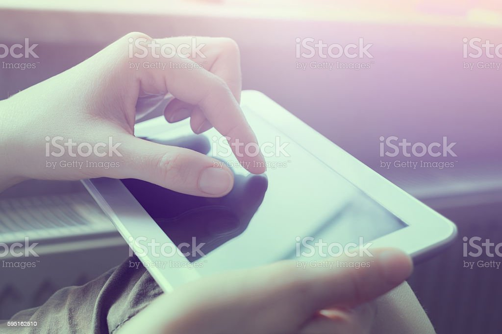 Woman Doing Zoom Gesture On White Tablet In Landscape View stock photo