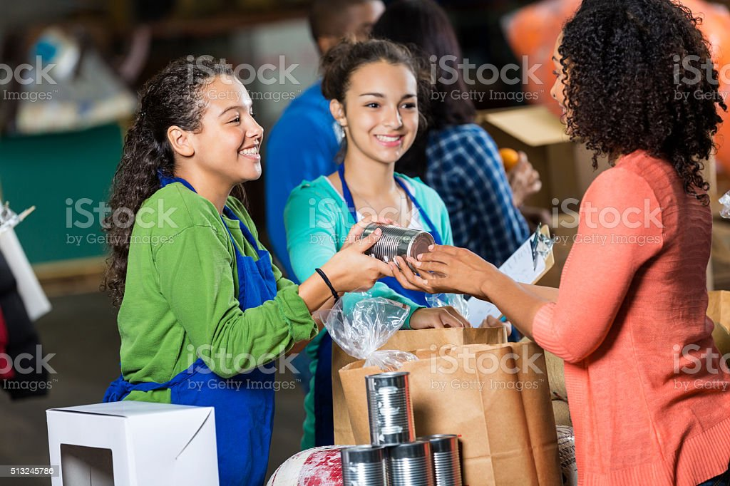 Woman donates canned goods to charity stock photo