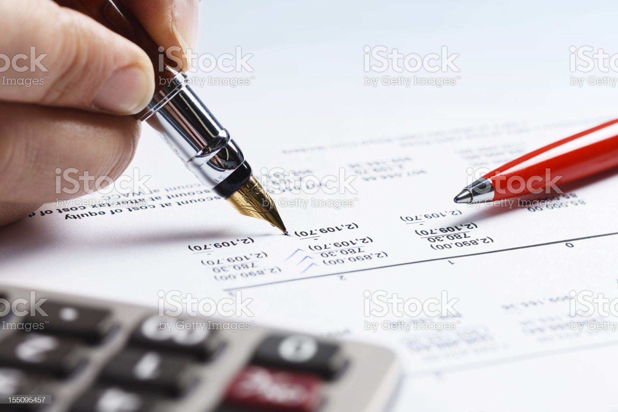 Woman double checking spreadsheet with fountain pen and ballpoint royalty-free stock photo