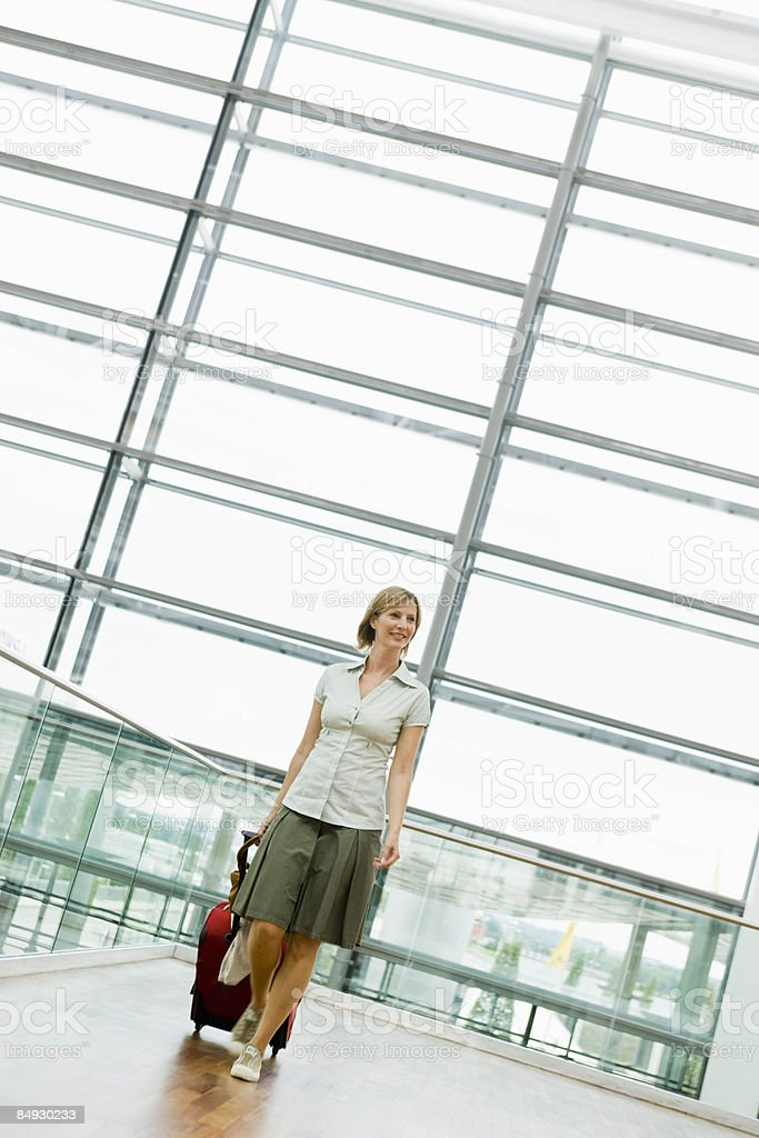 Woman dragging a suitcase stock photo