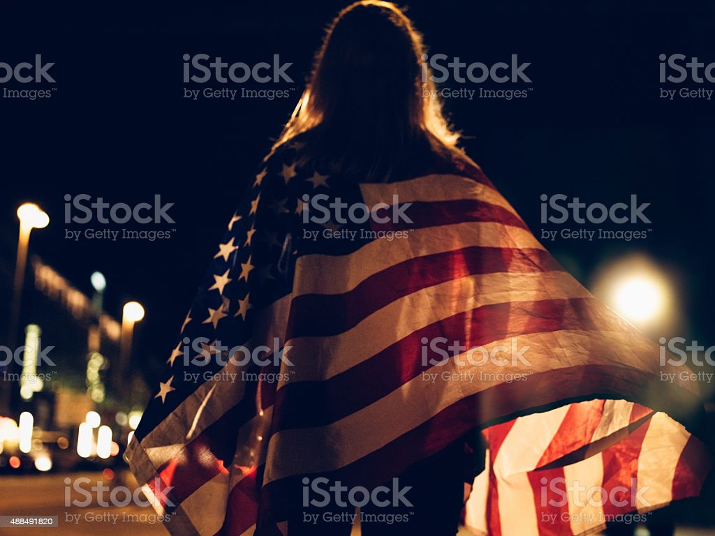 Woman draped with American flag on city street at night stock photo